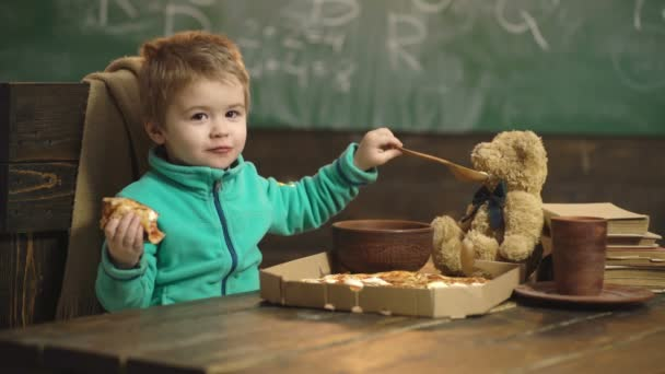 Junge isst Pizza auf einem hölzernen Hintergrund. Leckere Pizza. kleiner Junge mit einem Stück Pizza. Ernährungskonzept. Junge füttert den Bären mit einem Löffel. Babynahrung. Lustiges kleines Kind füttert einen Bären.
