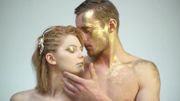 Sexy pár s golden těla umění make-up izolované na bílém. Zlaté lázeňských a kosmetických ošetření. Muž a žena vztahy. Zlatý kolagen maska a krásy. 24k Gold. Erotické hry, pár v lásce.