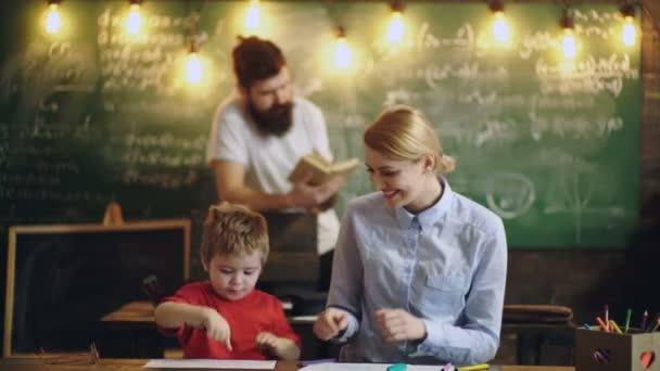 Eine Frau malt mit einem jungen in einer Schulklasse auf dem Hintergrund eines Mannes, ein Buch zu lesen. Junge zieht mit Lehrern. Learning-Konzepts. Klassenkameraden erziehen Freund wissen Lektion Konzept.