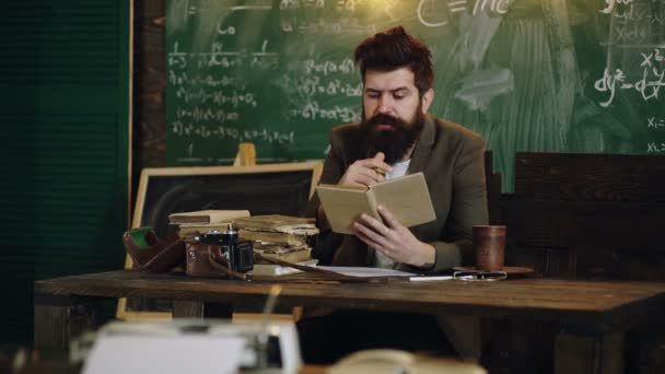 Education graduation and people concept. Bearded teacher reads a book in class. Teacher in classroom. Teacher and student. Back to school. Classmate Educate Friend Knowledge Lesson Concept.