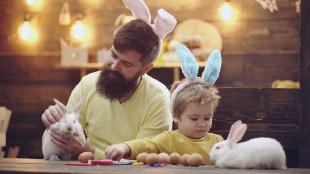 Šťastná rodina se připravují na Velikonoce. Na sobě uši zajíček roztomilý chlapeček dítě. Muž a chlapec kraslice na dřevěné pozadí.