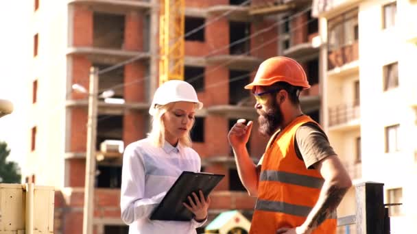 Builders communicate on the construction site. A woman in a white helmet communicates with a bearded man in an orange helmet and a protective vest on a construction site. Concept of construction.