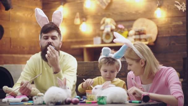 Boldog család készül a húsvét. Aranyos kis gyermek fiú nyuszi füle visel. Boldog tavaszi napon. Húsvéti tojás fa háttér. Vicces húsvéti állatok. Felkészülés a húsvéti ünnep.
