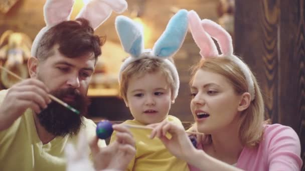 Mother, father and son are painting easter eggs. Happy family are preparing for Easter. Cute little child boy wearing bunny ears. Close-up portrait of cheerful family on the eve of Easter.