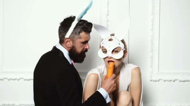 Couple with rabbit ears isolated on white background. Easter rabbits. Bunny couple. Happy couple preparing for Easter. Lovely man in rabbit costume is feeding his girlfriend bunny with carrot.