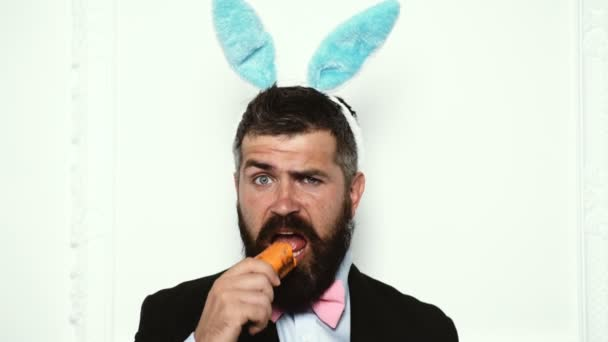Happy easter and funny easter day. Bunny rabbit man eat carrot isolated on white background. Cute bunny. Celebrating Easter. Ready to Easter. Funny man wearing bunny with carrot on spring day.