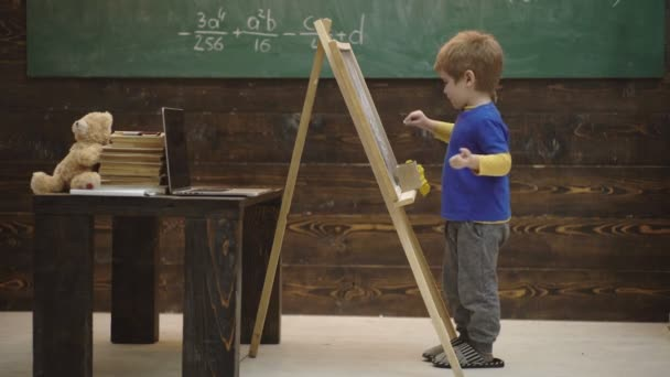 Vorschulerziehung. Kleiner Junge zeichnet mit Kreide auf Tafel. frühkindliche Bildung und Spielkonzept. Kreidetafel künstlerisches Lernen. Kreativität und pädagogisches Kunstspielzeug.