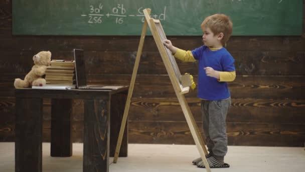 Dětský chlapec čerpá z tabule. Malý školák, co utíral tabuli. Zpátky do školních zpráv proti chlapečku s křídou na zelím. Koncept učení. Zpátky do školy. Učitel a student.