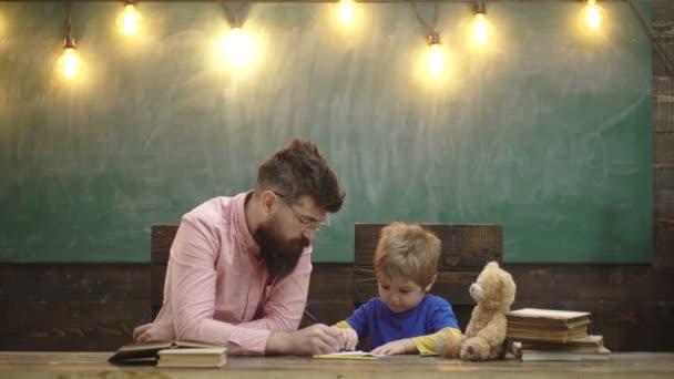 Teacher and small kid writing letters in copybook. Cute boy drawing a picture with colorful pencils. Art lesson at kindergarten. Learning concept. Teacher and student. Back to school.