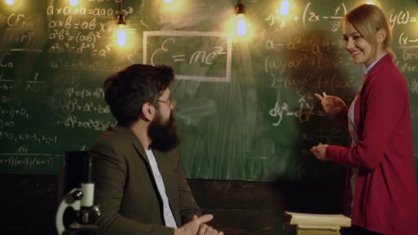 Amazed female student replies before teacher near board. Classmate Educate Friend Knowledge Lesson Concept. Teacher is sitting at table in classroom. Education, school, college and university concept.