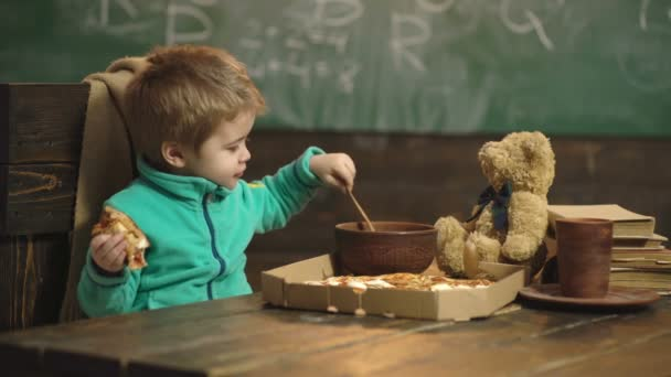 Feeding concept. Little child feeding teddy bear in school. Boy feeding and taking care of toy friend in classroom. Feeding your brain.