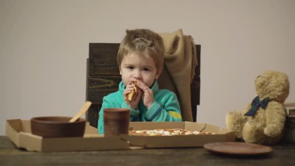 Chlapec se zakousne velký kus pizzy izolovaných na bílém pozadí. Roztomilý malý kavkazské chlapec jíst pizzu. Hladové dítě při kousnutí od pizzy. Chutná pizza.