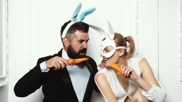 Eine Karotte wie ein Hase knabbert. Bereit für Party. Frohe Ostern. Bunny Mädchen essen Karotten und sieht sehr sinnlich. Paar mit Hasenohren. Hase-paar. Ostern, Make-up, Pin-up Party, Mädchen in Hasenohren.