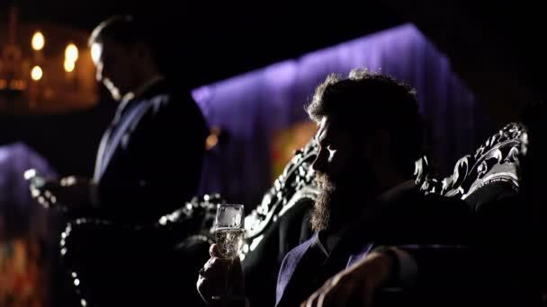 Alkohol, wohlhabender Lebensstil, Business, Geldkonzept. Krimineller Boss im Luxusanzug sitzt auf Vintage-Sofa. Kriminalität, Mafia, Gangsterkonzept. Luxus-Lifestyle. Bärtiger Mann mit ernstem Gesicht hält ein Glas.