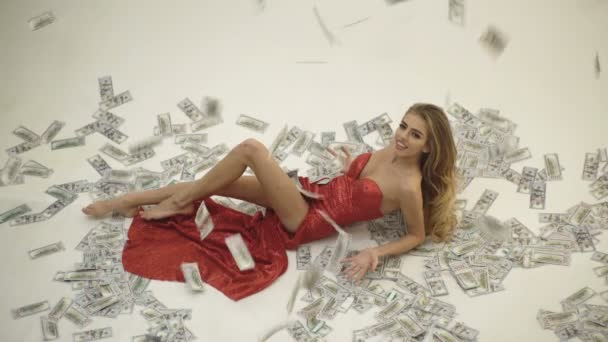 Currency, women, winning. Sexy woman lying in dollar bills. Girl in elegant red dress lying in banknotes. Rich woman lies on money. People, dollar, money, wealth and rich.