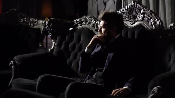 Confident handsome brunette man sitting in luxury interior. Adult successful elegant businessman wearing suit sitting in vintage sofa. Entrepreneur in elegant suit looks rich. Luxury rich lifestyle.