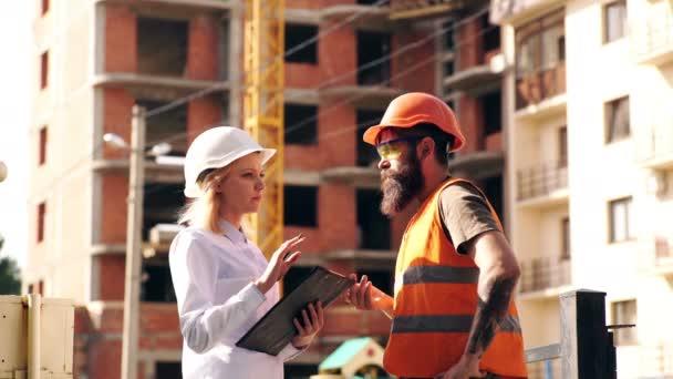 Usměvavý mladý architekt nebo inženýrský stavitel v tvrdé čepici se složkou v rukou nad skupinou stavitelů na staveništi, architekt, který sleduje stavbu, obchod, stavebnictví, průmysl