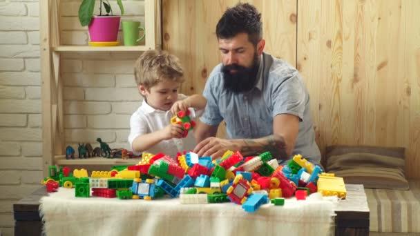 Rodina a dětství koncept. Muž a chlapec hrát společně na dřevěné stěně obrazce pozadí. Táta a dítě stavět z plastových bloků. Otec a syn s zaneprázdněn tváře vytvoření barevné konstrukce s hračka cihly