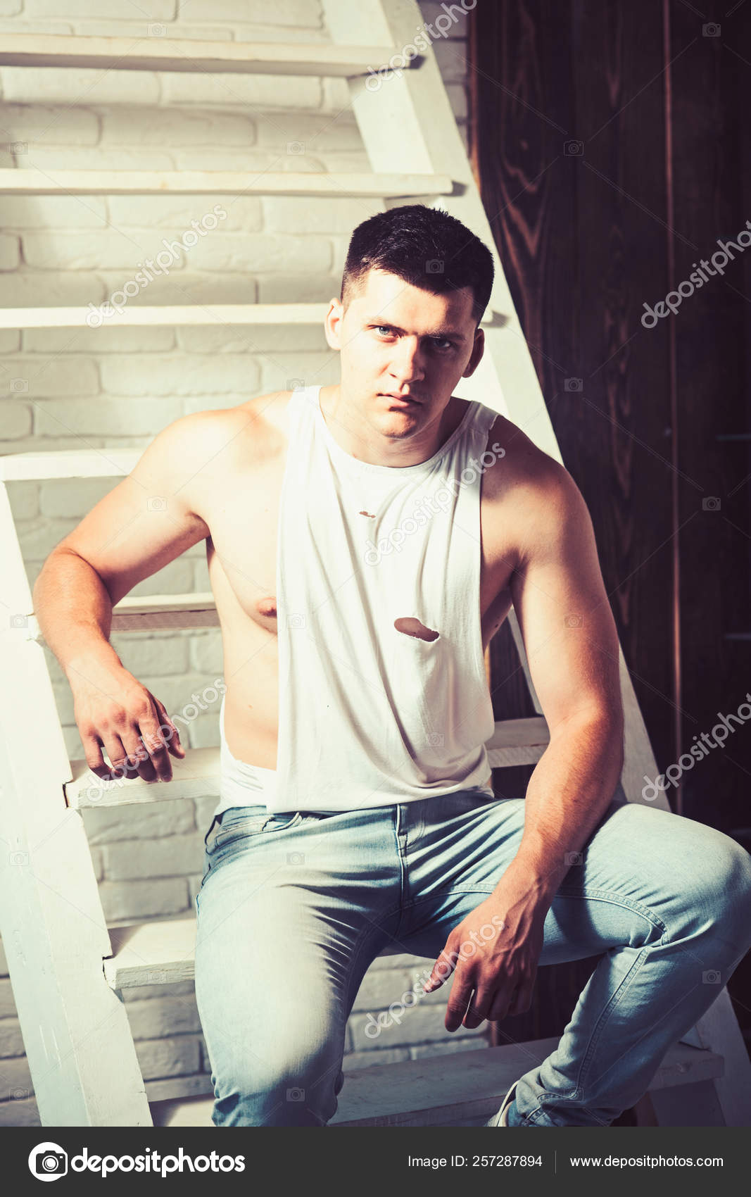 e5d459e49fbd3 Athletic macho with muscular chest and hands. Young man sit on ladder. Guy  in trendy tank top ...