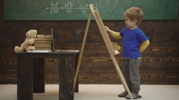 Lovely toddler boy drawing on chalkboard on wooden background. Small artist paints on a wooden background. Concept of fine art. Smart little fellow studying math. Learning concept. Back to school.