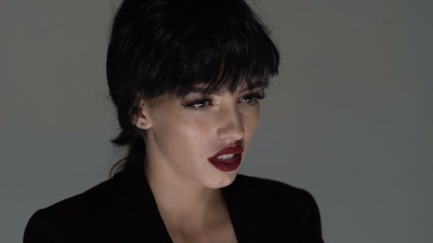 Young brunette woman with red lips screaming isolated on grey background. Concept of acting art. Desperate female screaming in sorrow. Portrait of pretty girl shouting. Woman screams, panic, scream.