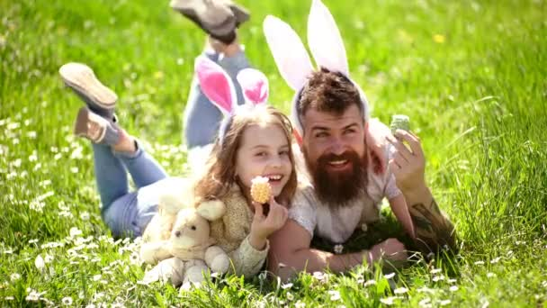 Dad and girl found easter eggs in traditional hunting game in. Man with beard and cute child lay on grass with easter egg in hand. Father and child with bunny ears lying at meadow. Teamwork concept.