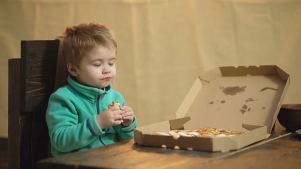 Boy eating pizza on a wooden background. Tasty pizza. Little boy having a slice of pizza. Hungry child taking a bite from pizza. Concept of nutrition.