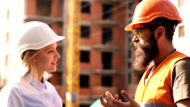 Construction worker and engineer talking at construction site site. Workers in helmets at building area. Portrait of construction engineers working on building site. concept of modern construction.