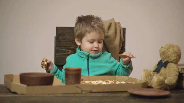 Pozadí. Chutná Pizza. Malý chlapec má kousek pizzy. Hladový dítě si kousne pizzu. Pojem výživy. Chlapec v zeleném svetru sní pizzu při sezení na dřevěném křesle.