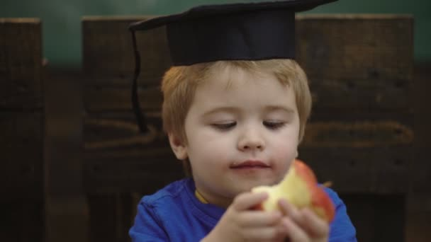 Boy with graduate hat and apple. Learning concept. School children in uniform. Teacher and student. Back to school. Classmate Educate Friend Knowledge Lesson Concept.