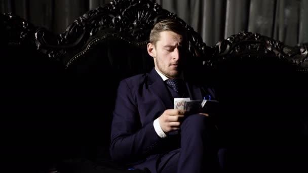 Luxury life concept. Man in suit, businessman sit in dark luxury interior background. Luxury rich lifestyle. Entrepreneur in elegant suit looks rich. Man counts money in an expensive interior.