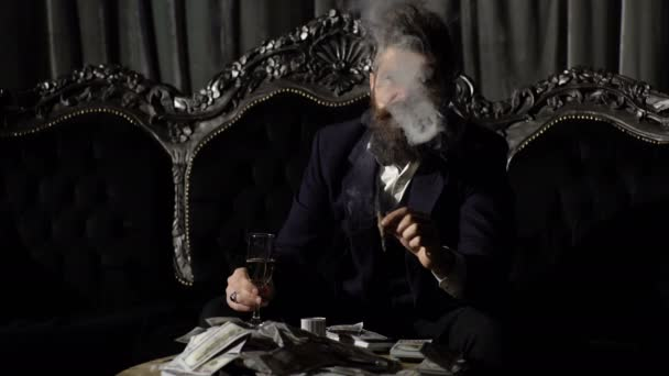 Criminal boss in luxury suit sits on vintage sofa. Crime, mafia, gangster concept. Luxury rich lifestyle.Entrepreneur in elegant suit looks rich. Bearded man champagne glass and smoke cigar.
