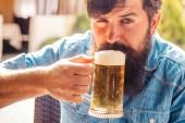 Starší muž pije pivo. Pivní čas. Retro reklama na alkoholické nápoje. Retro muž s pivem.