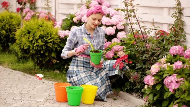Starat se o květiny. Krásná mladá žena užívající přírodu v jarní hortenzie zahradě. Šťastná krásná blondýnka v zahradě s kvetoucí růžovou hydrangiou. Romantický módní model v květinách.