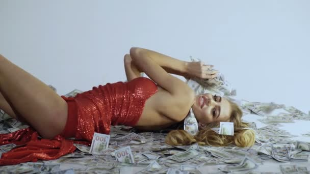 Proud woman in elegant red dress lying on banknotes. Rich woman. Business concept. Woman with lot of money. Saving money concept. Business success concept. Digital money concept. Finance.