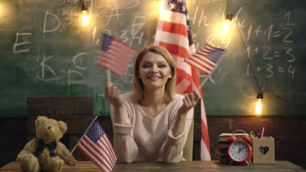 Young girl student on the background with American flag. English language learning concept. English, studying, speak. Portrait of cute confident smiling student lady emigrant.
