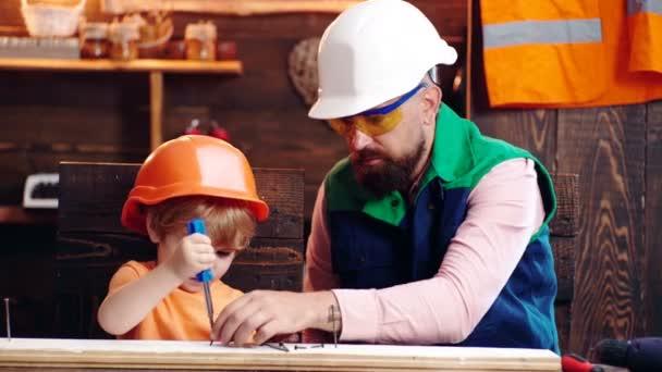 Apa, szülő szakáll tanítás kisfiát használni szerszám csavarhúzó. Fiú, gyermek foglalt védősisak tanulás használni csavarhúzót apával. Kis asszisztens koncepció. Handyman koncepció. Csapatmunka.