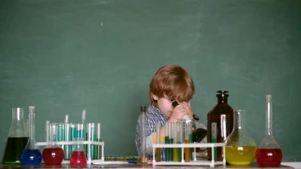 Bambino della scuola elementare. scolaro. Il piccolo scienziato dei bambini che fa chimica in laboratorio scolastico. Esperimenti di biologia al microscopio. Concetto di scienza ed educazione.