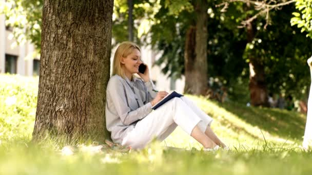 Female student speaks by phone and writes a diary in the park. Natural environment office. Work outdoors benefits. Online dream job. Female student studying in a park sitting on a grass.
