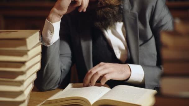 Kaukázusi Férfi olvasás, fordult a könyv oldalain, egy csomó könyvet a táblázatban. Szakállas férfi könyv olvasatban a fából készült asztal csokor könyvek. A könyvtári könyvek és a tanulmányaik fogalma.