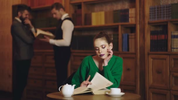 Woman in library read book and drinking coffee from cup  Literature cafe  with cute girl and mens on background  Student life in university  Concept  of reading book and study poetry