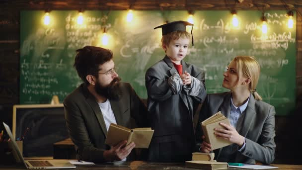 Home tutor helping boy with studies using modern laptop. Teacher sets high expectations for his students. Learning and people concept. Lesson with qualified private tutor. Boy in graduation hat.