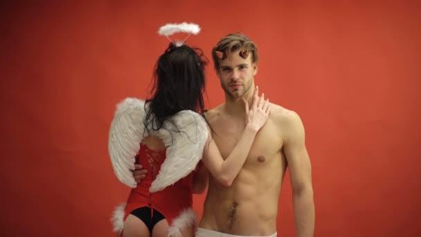 Engel und Teufel. sexy Paar isoliert auf rot. sexy Engelsfrau berührt den nackten Oberkörper des Teufelsmännchens auf rotem Hintergrund. sexy Paar, das Sexspiele spielt. Süßer Engel und Teufel. Es ist Liebe.
