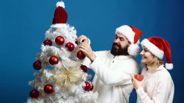 Család, x-mas, téli ünnepek, és az emberek fogalmát. Boldog pár díszítő karácsonyfa és teát inni több mint kék háttér. Boldog család díszíteni karácsonyfát. Kellemes karácsonyi ünnepeket és boldog új évet.