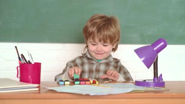 Iskolai koncepció. Általános iskola. Gyerekek iskolába. Szeptember 1. Kisfiú az osztályteremben. Oktatás először. Boldog hangulat mosolyogva nagyjából az iskolában.