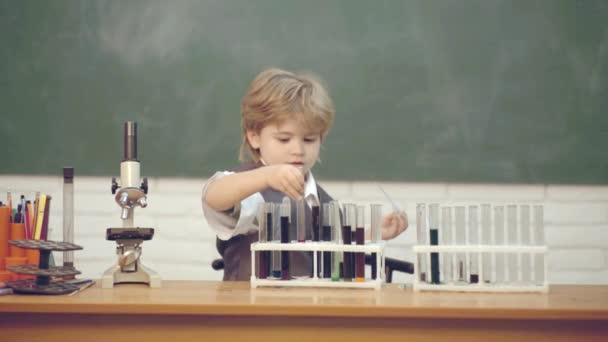 Bambino nella classe con lavagna sullo sfondo. Microscopio di laboratorio e tubi di prova. Scuola a casa. Il mio esperimento di chimica. Chimica per il juniores.