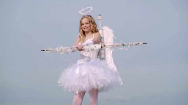 Kisgyermek lány visel angyal jelmez fehér ruhában és toll szárnyak. Valentin-nap Ámor. Valentin-nap. Ártatlan lány. Ünnepi művészeti üdvözlőlap
