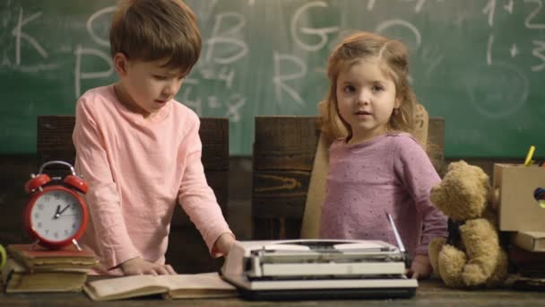 Zpátky do školy. Chlapec a dívka sedí u stolu s psacím strojem na pozadí zelené školní tabule. Vzdělat koncept znalostí. Šťastné děti se baví. Pozadí. Vzdělání a dětství.