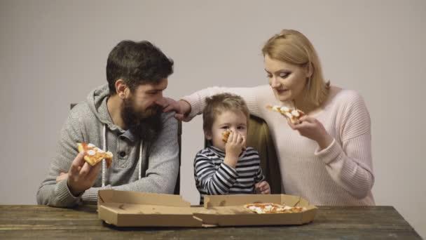 Leckere Pizza. Kleiner Junge mit Eltern, die Pizza essen. Hungriges Kind beim Pizzaessen. Ernährungskonzept. isoliert auf weiß. Familie isst eine leckere Pizza. Hintergrund. weißer Hintergrund.