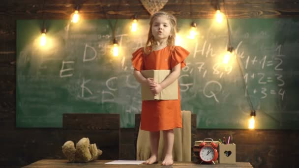 Girl in a red dress with a book in her hands stands on the table in the school class. Back to school. Teacher helping pupil in classroom at the elementary school. Lesson with qualified private tutor.